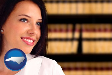 a young, female attorney in a law library - with North Carolina icon